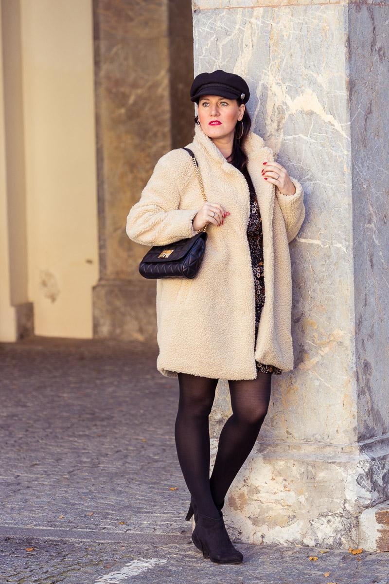 Outfit mit Teddy Coat und Blumenkleid: Fashionbloggerin Miss Classy aus Graz trägt Blumenkleid mit schwarzer Strumpfhose, dazu einen weißen, kuscheligen Teddy Coat, einen Baker boy Hat und schwarze Stiefeletten. Die Handtasche ist von Michael Kors. Fashionblog, Modeblog, Fashion Blog Graz, Miss Classy
