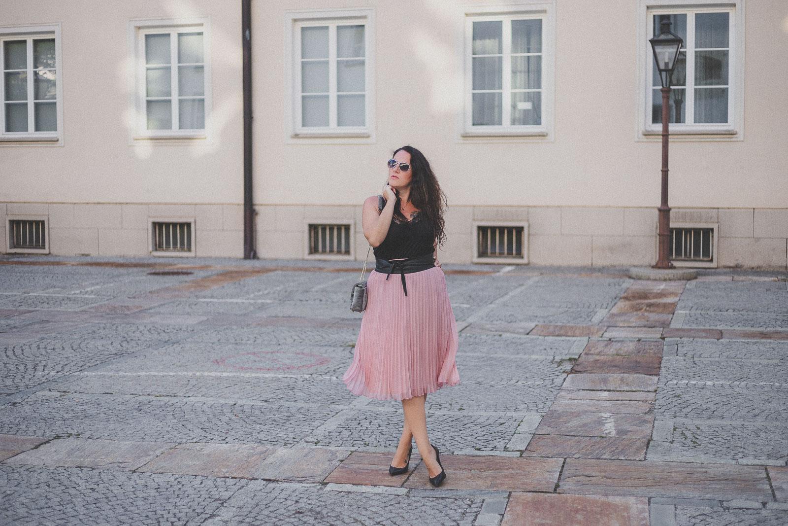 Rosa Plisseerock mit schwarzem Lace-Top und High Heels