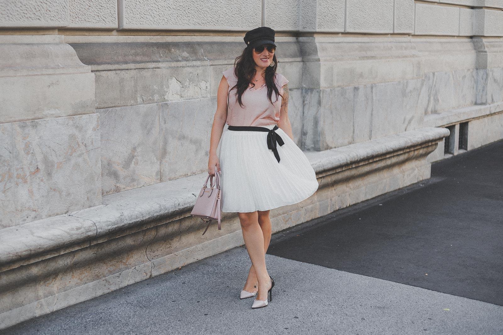 Sommerliches Outfit mit weißem Plisseerock, rosa Bluse und High Heels