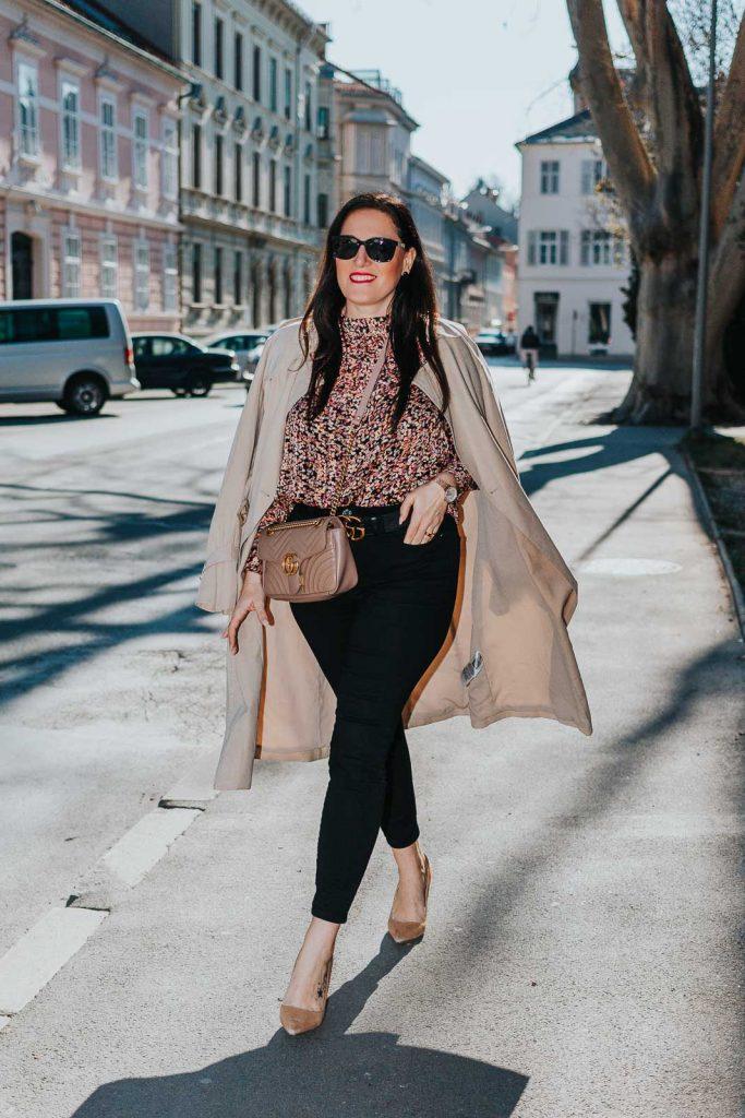 Modebloggerin Miss Classy trägt ein Outfit mit Trenchcoat von Guess, einer schwarzen Skinny Jeans, einer gemusterten Bluse und Pumps. Als Accessoires trägt sie einen Gürtel von Gucci mit Doppel G Schnalle und die Gucci Marmont Schultertasche.